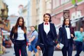 Beautiful girls in black suits walking the street — Stock Photo