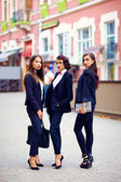 Beautiful girls in black suits posing on the street — Stock Photo