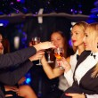 Beautiful women clinking glasses in limousine — Stock Photo #53620099