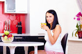 Pregnant woman drinking fresh juice in kitchen — Stock Photo