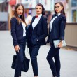 Beautiful girls in black suits posing on the street — Stock Photo #54396247