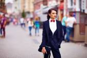 Beautiful elegant woman posing on crowded city street — Stock Photo