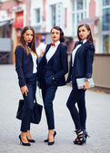 Beautiful girls in black suits posing on the street — Stockfoto