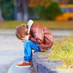 Upset kid boy sitting alone in city park — Stock Photo #54498853