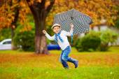 Happy stylish boy with umbrella running in park — Stock Photo