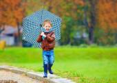 Happy boy running under an autumn rain — Stock Photo