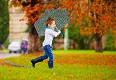 Cute boy enjoying an autumn rain in city park — Stock Photo