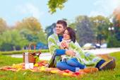 Happy couple enjoying autumn picnic in city park — Foto de Stock