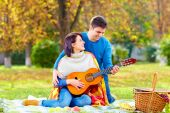 Man teaching girl play a guitar on autumn picnic — Stock Photo
