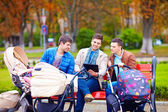 Three happy fathers with buggies in city park — Stock Photo