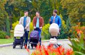 Three friends, fathers walking with buggies in city park — Stock Photo