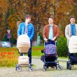 Fathers walking with buggies in city park, parental leave — Stock Photo #55065661