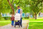 Father with kids walking in city park — Stock Photo