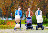 Fathers walking with buggies in city park, parental leave — Stock Photo