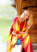 Positive woman enjoying autumn, wrapping herself in warm blanket — Стоковое фото