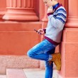 Stylish teenage boy listens to the music on smart phone — Stock Photo #56095067