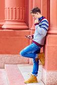 Stylish teenage boy listens to the music on smart phone — Stock Photo