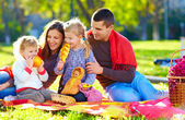 Happy family on autumn picnic in park — Stock Photo