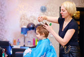 Little client, boy having haircut at hair salon — Stock Photo