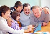 Group of happy people with disability having fun with tablet — Stock Photo