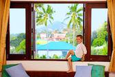 Cute boy sitting on window sill in tropics — Stock Photo