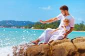 Water splashing on happy father and son on vacation — Stock Photo