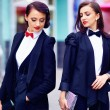 Two gorgeous women posing in black suits — Stock Photo #65425761