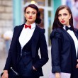 Two gorgeous women posing in black suits — Stock Photo #65425779