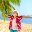 Young fashionable boy enjoys life on tropical beach — Stock Photo #65953931