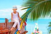 Cute fashionable boy posing on old boat at tropical beach — Zdjęcie stockowe