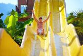Uomo emozionante divertendosi sulla scivolo d'acqua nel parco acquatico tropicale — Foto Stock