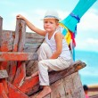 Cute kid, boy sitting on old boat on tropical beach — Stock Photo #66787995