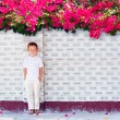 Cute boy kid standing near blooming wall — Stock Photo #66788271
