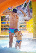 Happy excited family under water stream in water park — Foto Stock