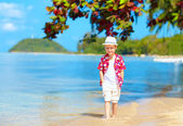 Cute kid boy walking in water on tropical beach — Stock Photo
