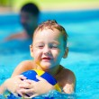 Cute kid playing water sport games in pool — Stock Photo #66918393