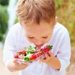 Cute boy tasting yummy fresh strawberries in sugar powder — Stock Photo #67080385
