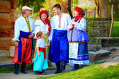 Happy ukrainian family in traditional costumes on their homestead — Stock Photo