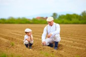 Grandpa explaining his grandson the way plants are grow — Stock Photo