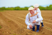 Happy farmer family having fun on spring field — ストック写真