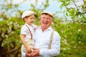 Happy grandfather and grandson having fun in spring garden — Stock Photo