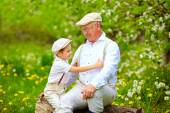 Grandson playing with grandpa in spring garden — Stock Photo