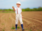 Cute little farmer on spring field  holding earth clod — Stock Photo