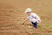 Cute little farmer spuding the soil on spring field — Stock Photo