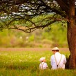 Father and son sitting under the tree on spring lawn — Stock Photo #72146231