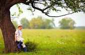 Cute little boy under the big blooming pear tree, countryside — Stock Photo