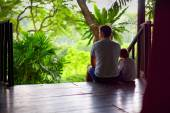 Father and son sitting on tree house stairs in tropical forest — Stock Photo