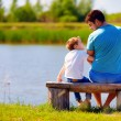 Happy father and son sitting on the river bank — Stock Photo #73362919