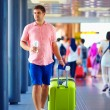 Young adult man walking through crowded international airport — Stock Photo #73607867