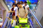 Happy family with baggage on conveyor in airport, ready to travel — Stock Photo